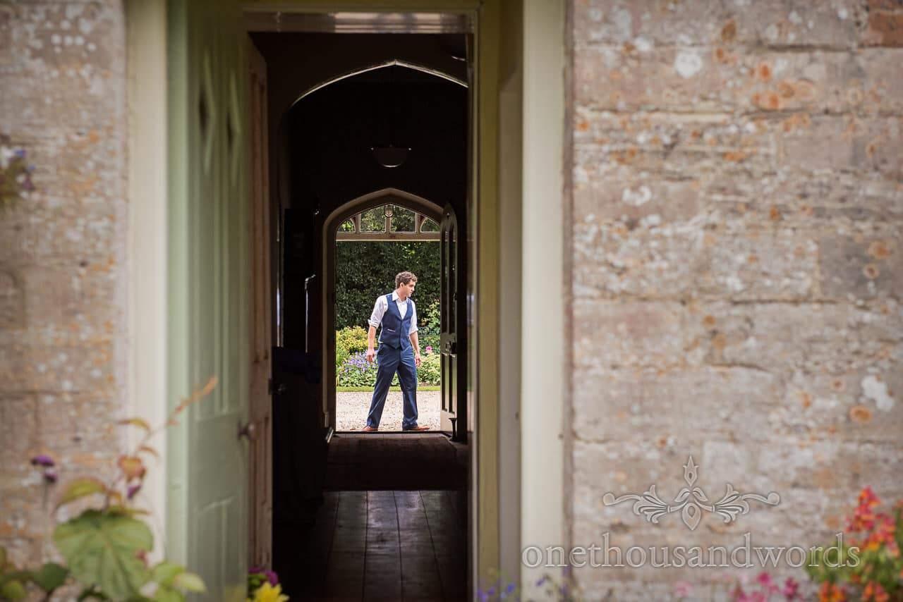 Groom through doorway from Dorset garden wedding