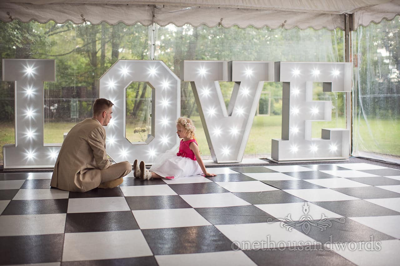 Groomsman and flower girl sit on dance floor at Old Vicarage Wedding Photographs