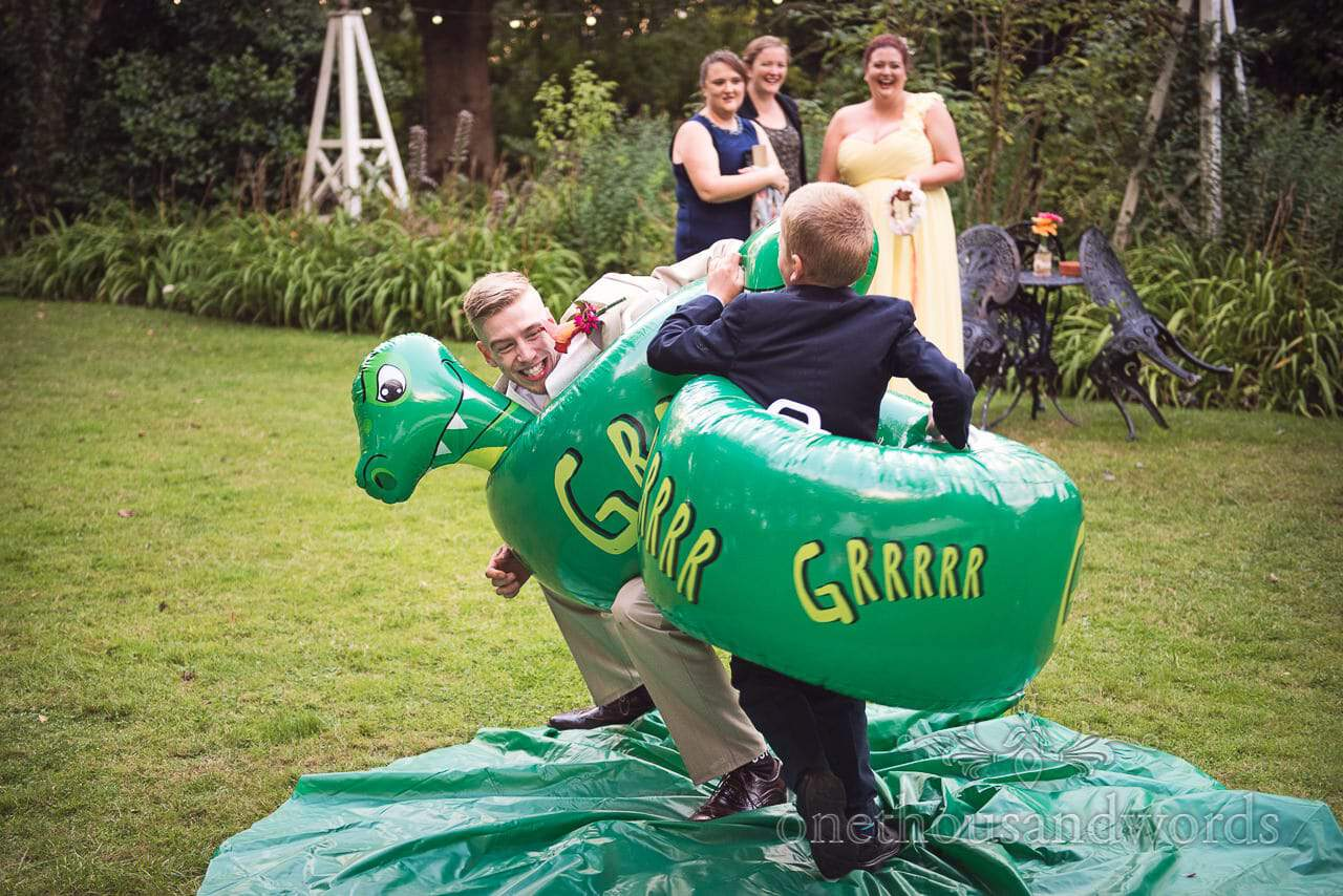 Groomsman and young guest enjoy inflatable game at Old Vicarage Wedding Photographs
