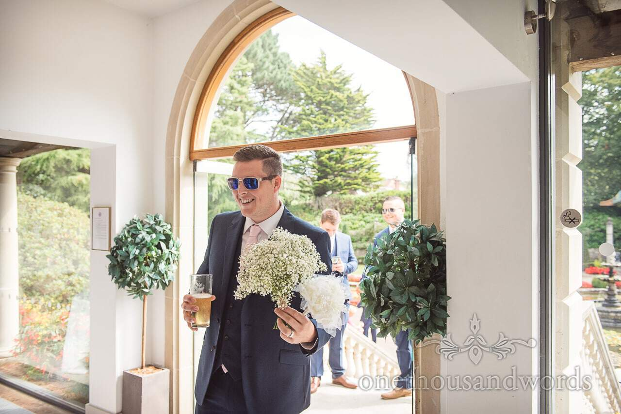 Groomsman with bouquets and beer at the Italian Villa Wedding venue Photos