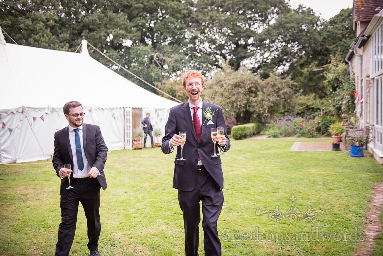 Groomsman delivers drinks during reception at garden wedding