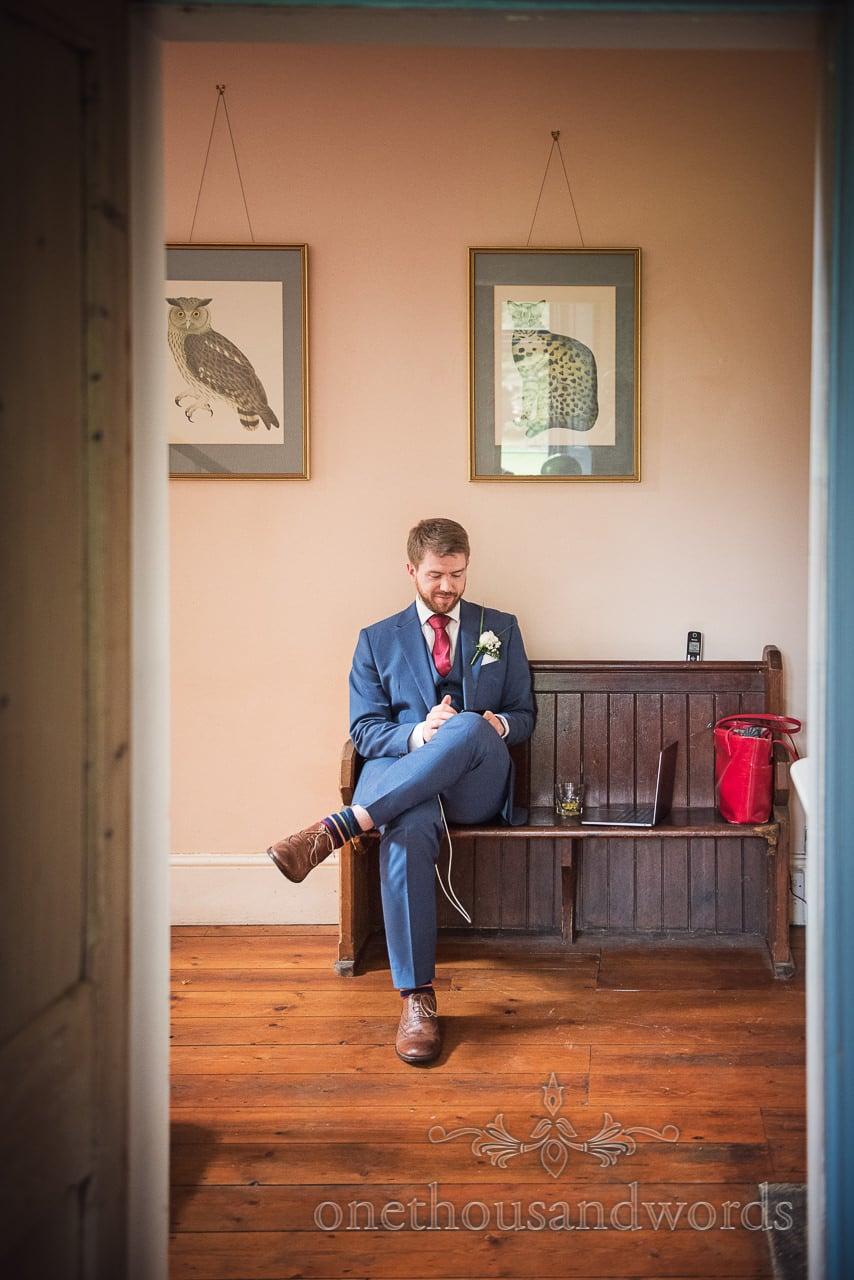 Groomsman takes a seat inside house at Garden wedding