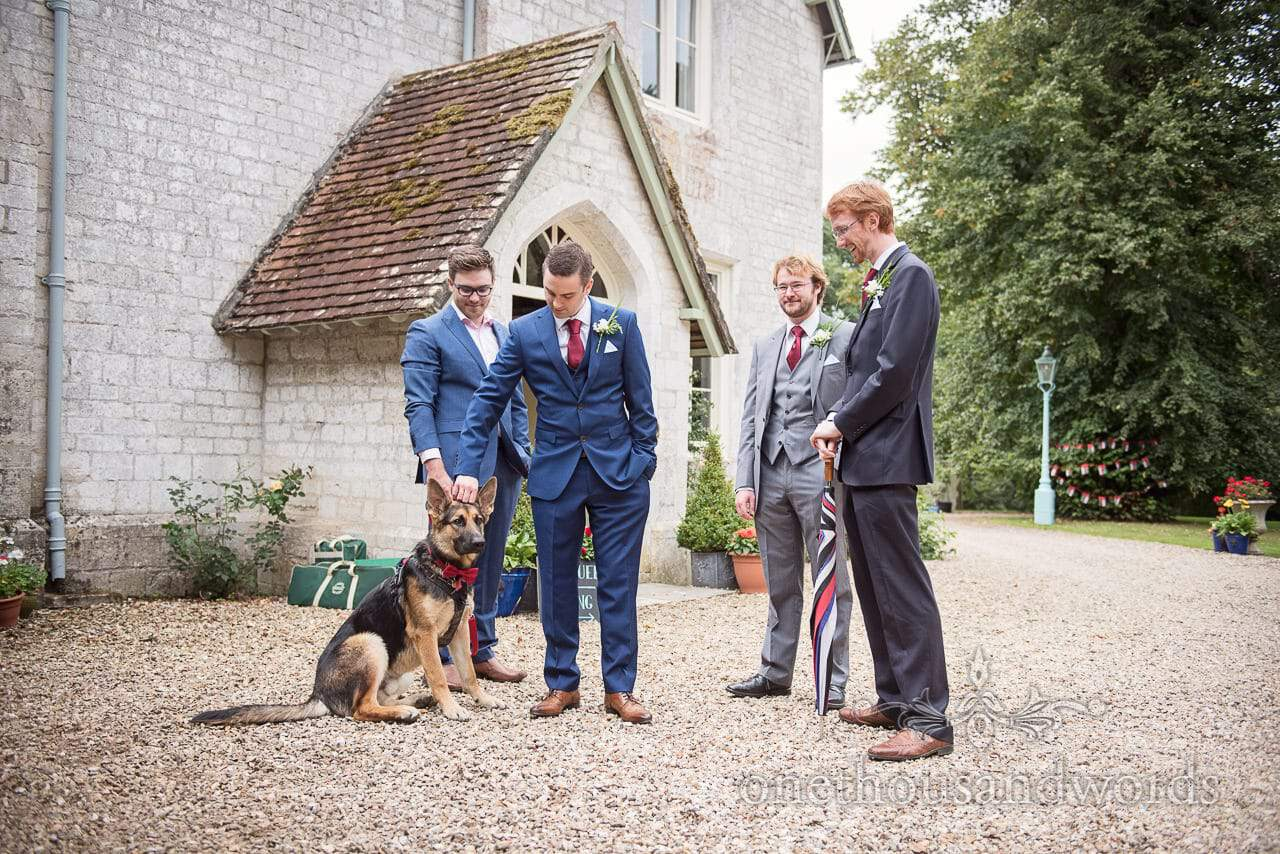Groomsmen and family dog await arrival of bridal party for garden wedding