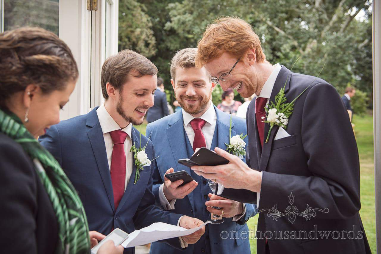 Groomsmen check running order of the day at Dorset garden wedding