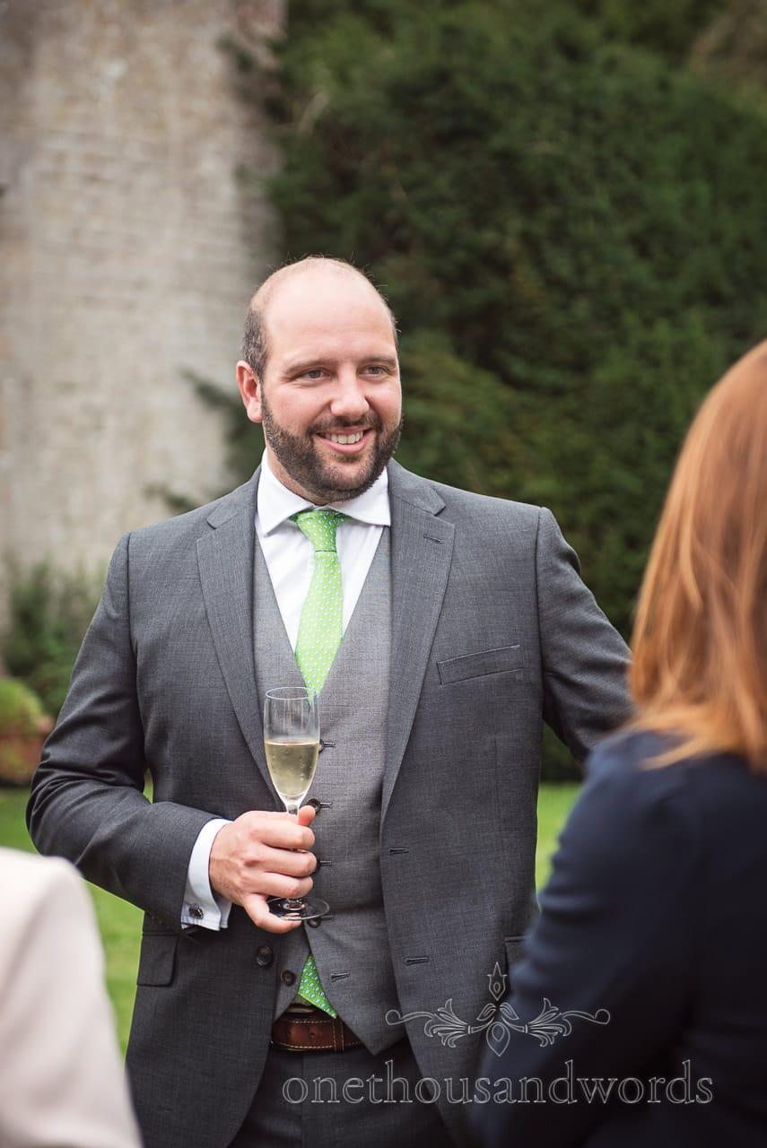 Guest in grey three piece suit during drinks reception at Dorset garden wedding