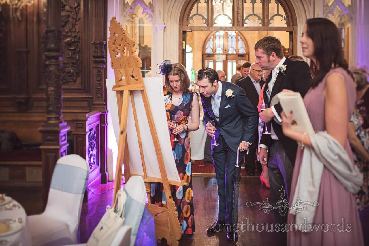 Guest look at table plan in great hall at Canford School Wedding