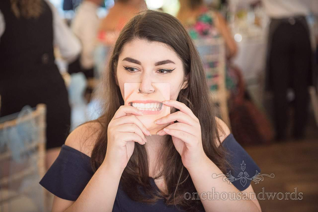 Guest poses with funny face card during reception at Italian Villa
