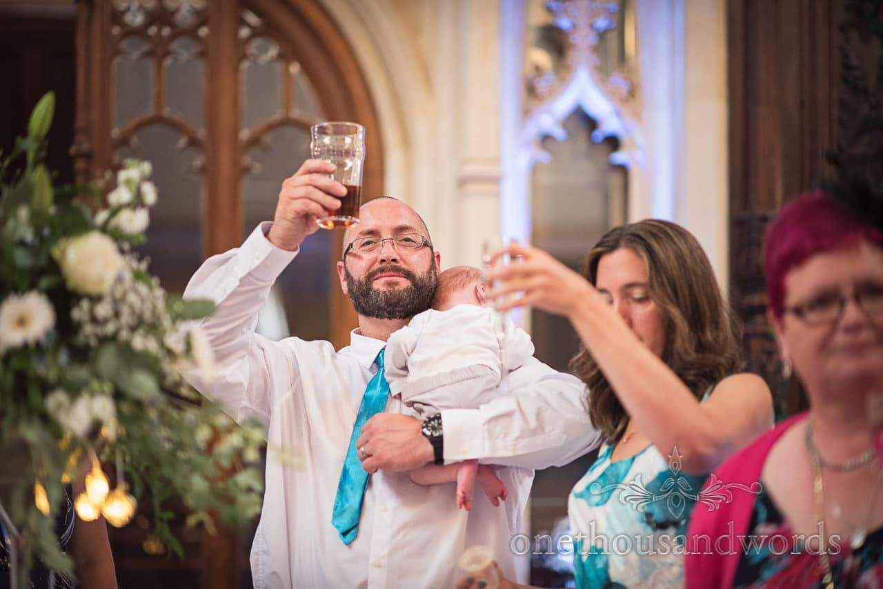 Guest raises glass to toast while holding baby Canford School Wedding