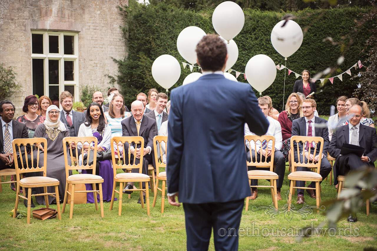 Guest reaction to hearing that the bride has arrived at Dorset garden wedding
