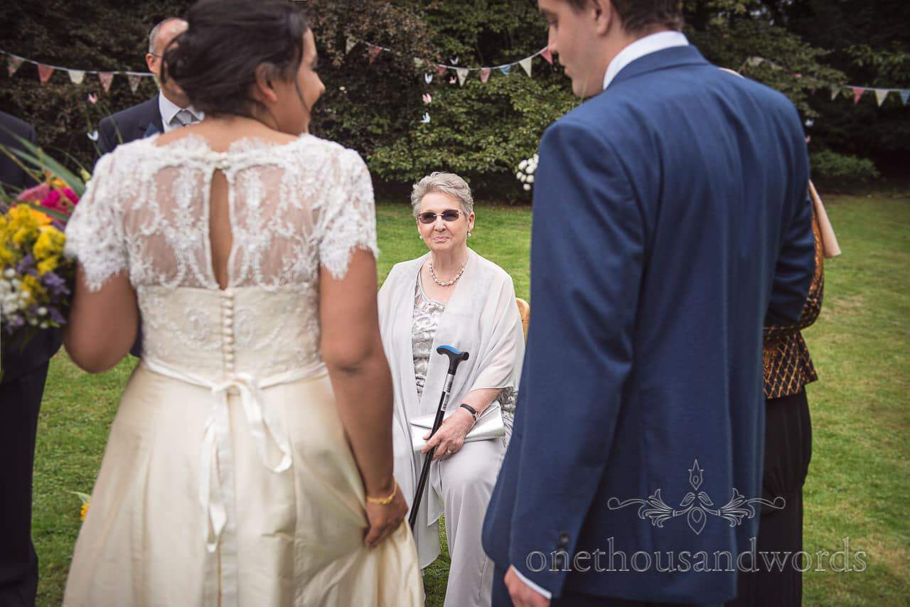 Guest sits during drinks reception at garden wedding