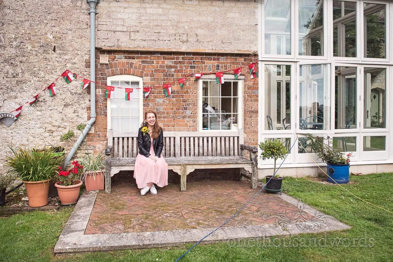 Guest take a seat on garden bench at Dorset garden wedding