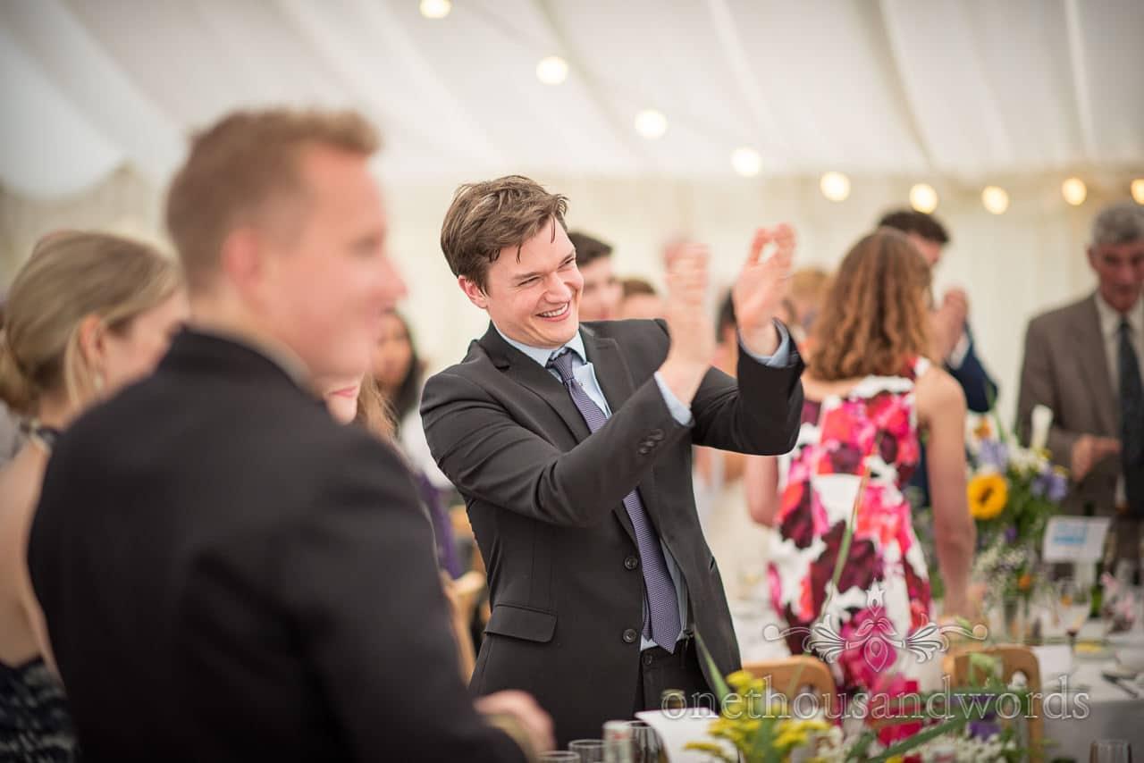 Guests applaud during speeches in marquee from garden wedding