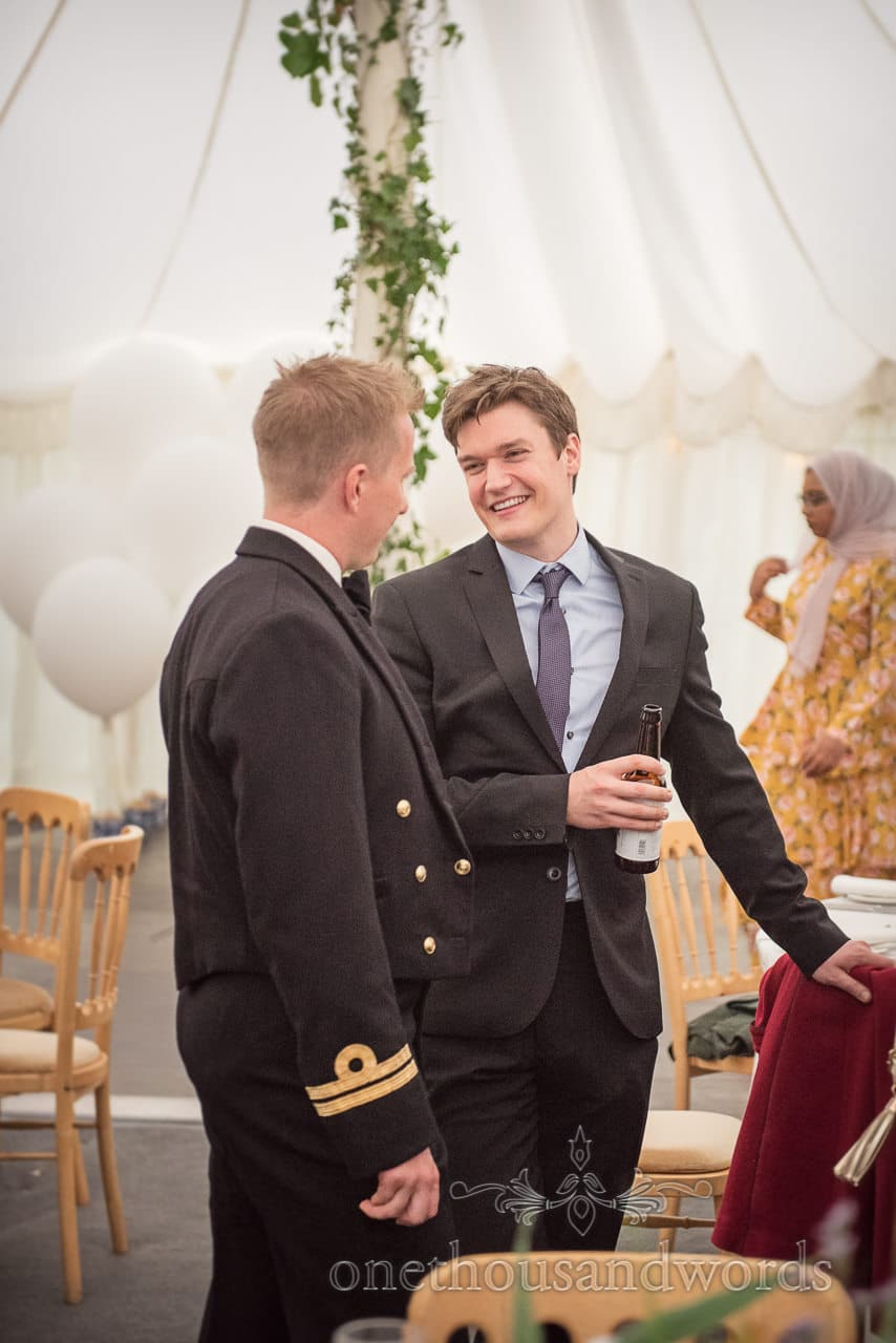 Guests chat over a drink in marquee at Dorset garden wedding