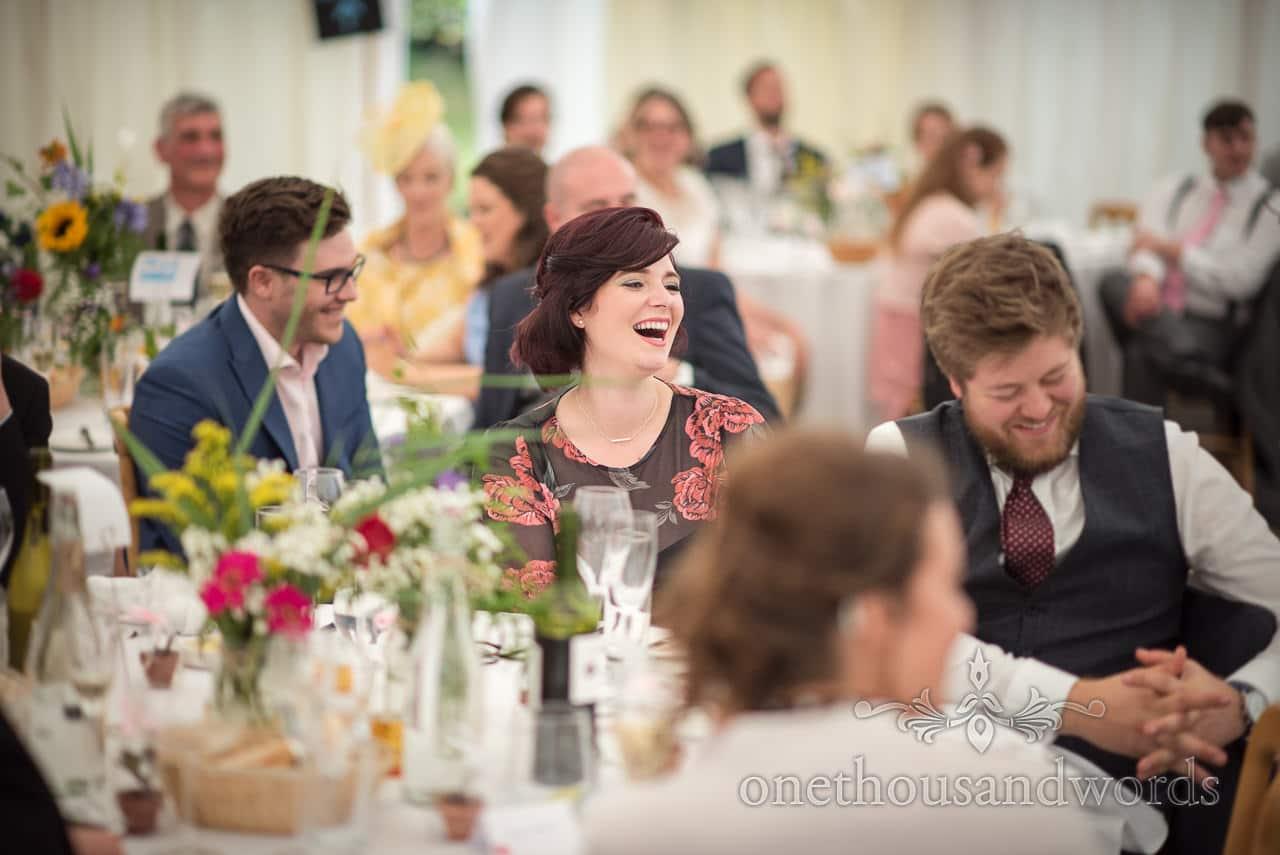 Guests laugh during speeches in marquee garden wedding reception