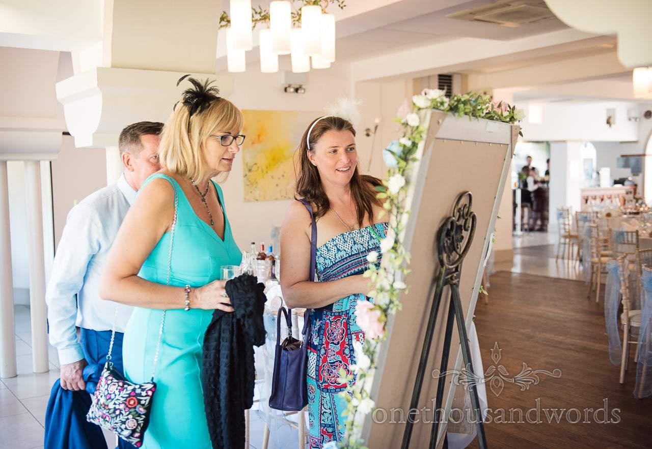 Guests look for name on table plan at Italian Villa Wedding venue photos