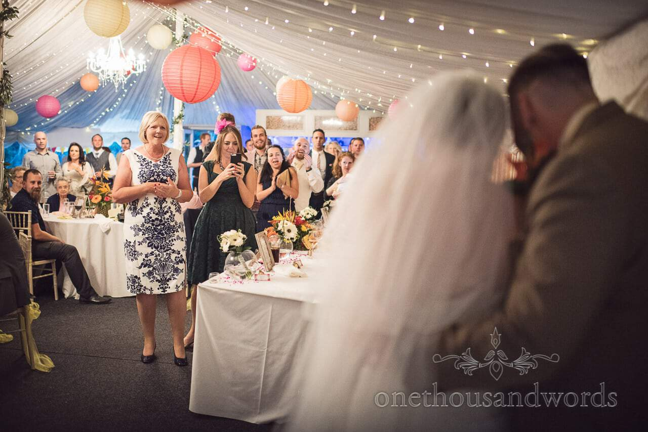 Guests look on as bride and groom cut cake at the Old Vicarage Wedding Photographs
