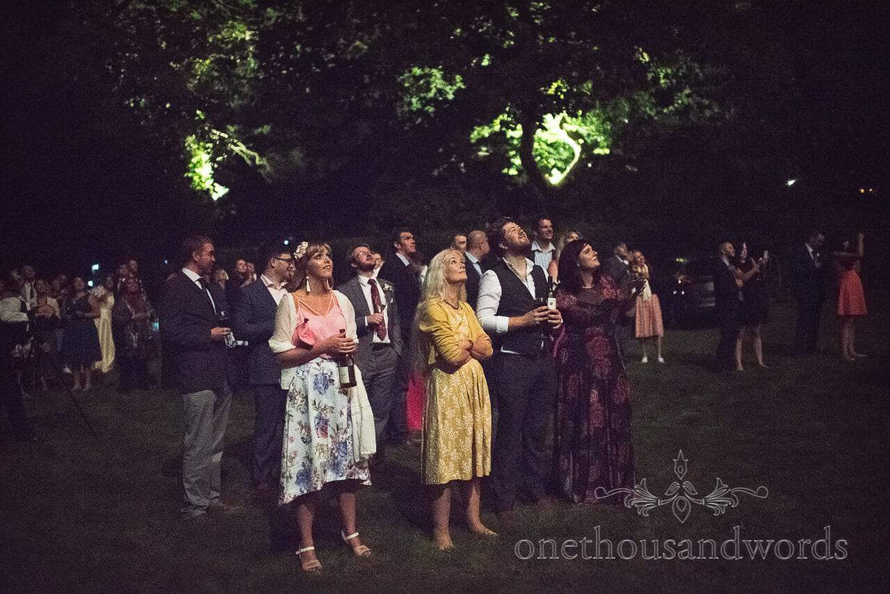 Guests look up at fireworks display at garden wedding