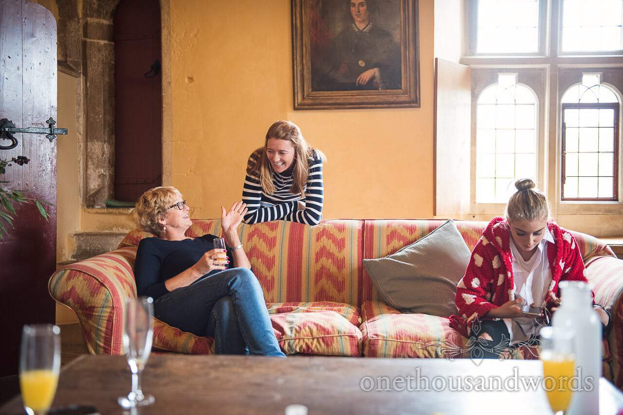 Guests share a joke at Woodsford castle during morning of Garden Wedding