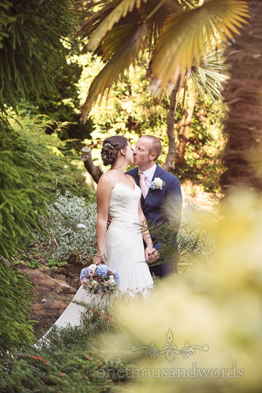 Kissing bride and groom in rock and water garden at Compton Acres
