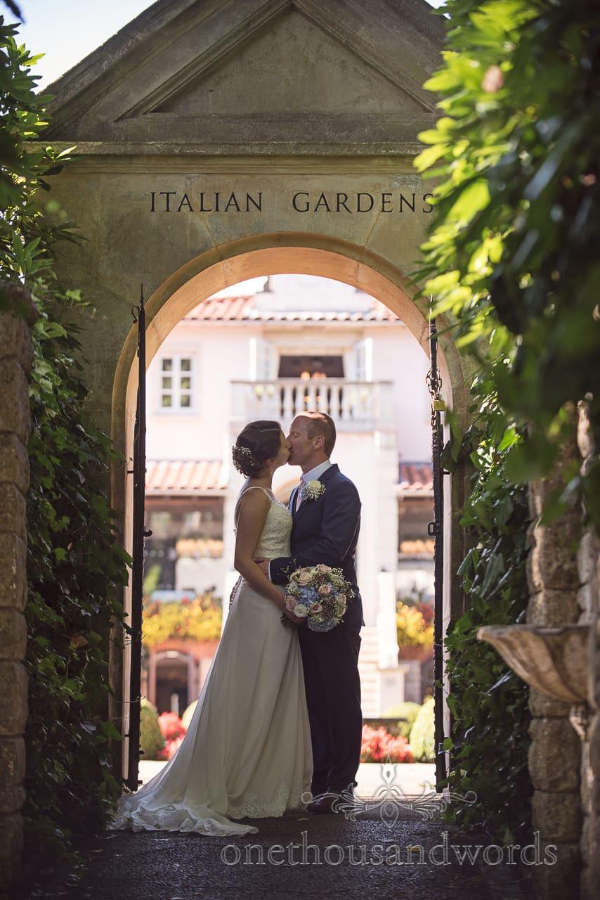 Kissing couple in archway at the Italian Villa Wedding venue photos