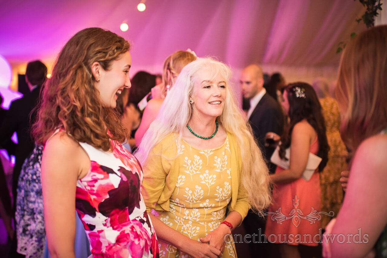 Mother and sister of the groom on dance floor at marquee wedding reception