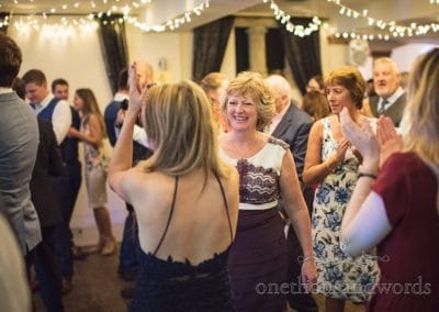Mother of the bride dances with wedding guests on wedding dance floor