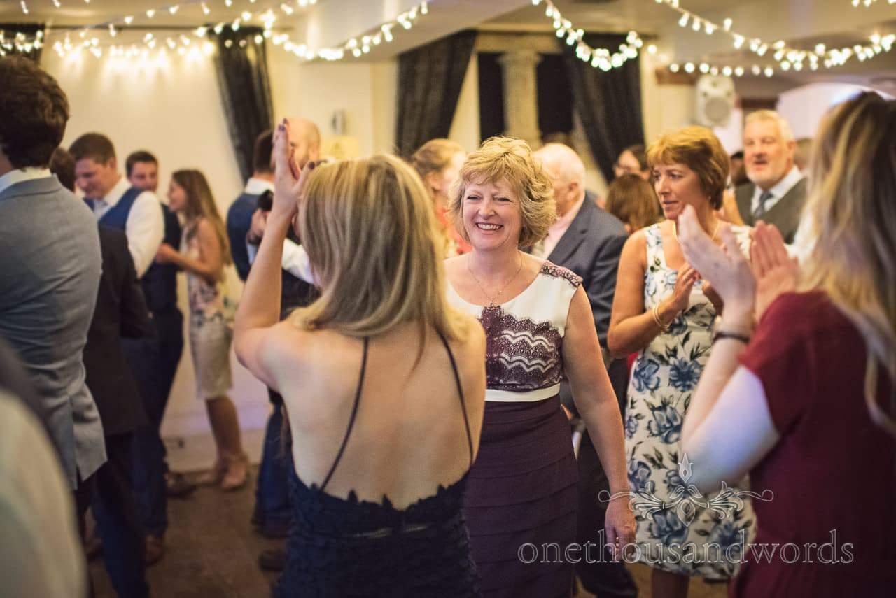 Mother of the bride dances with wedding guests on wedding dance floor