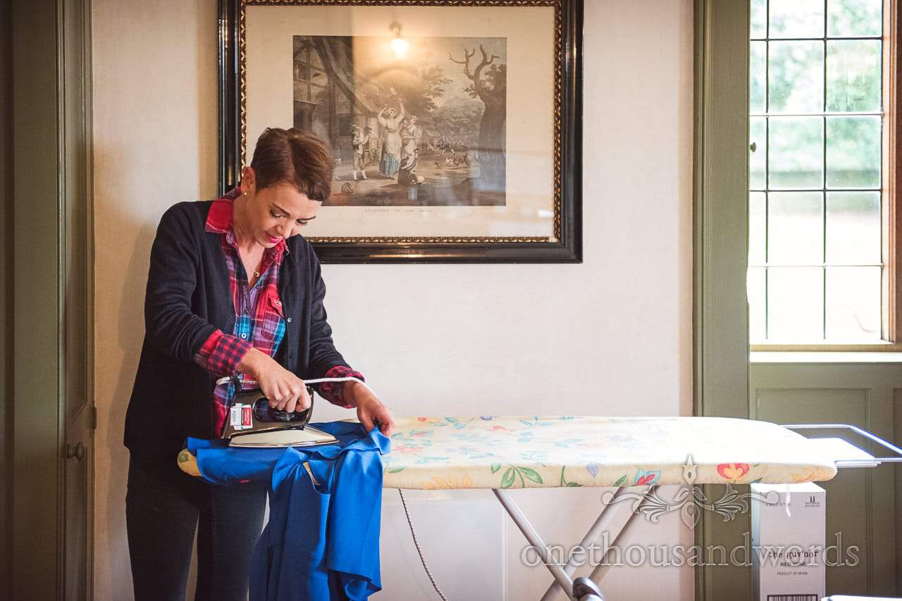 Mother of the bride ironing on wedding morning at Woodsford castle