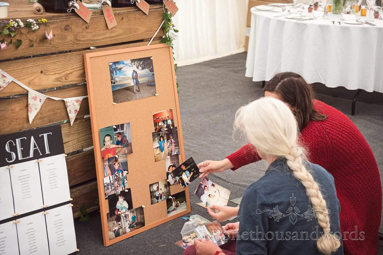 Mother of the groom and friend select photos for pin board at Dorset Garden Wedding