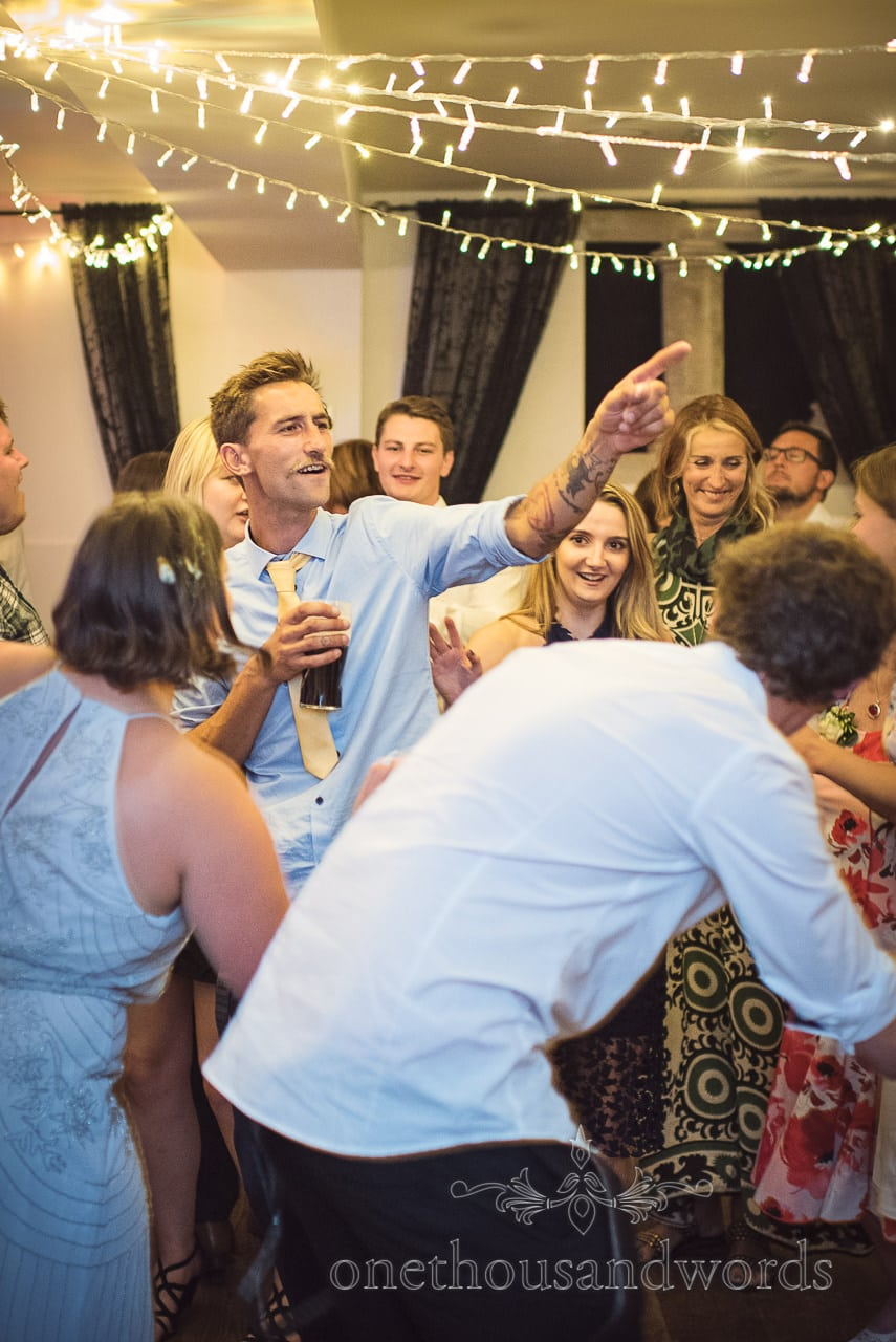 Moustached wedding guest points during wedding dancing under fairy lights