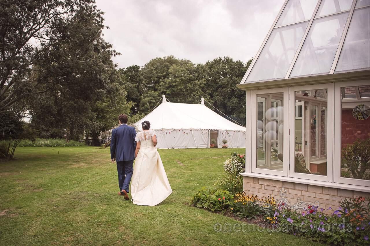 Newlyweds walk towards marque at Dorset garden wedding