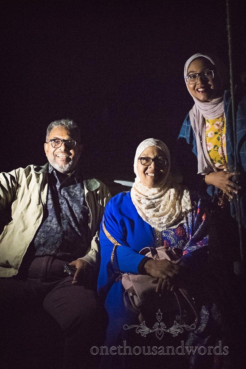 Nighttime family portrait during fireworks at garden wedding