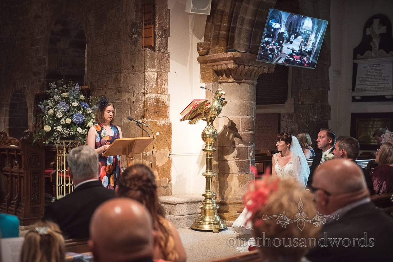 Reading is delivered in Norman church at Canford School Wedding