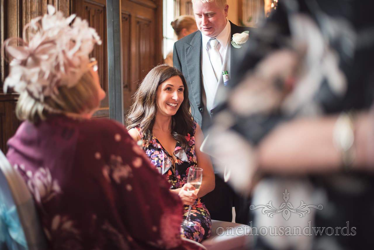 Seated guest during drinks reception in long gallery at Canford School Wedding