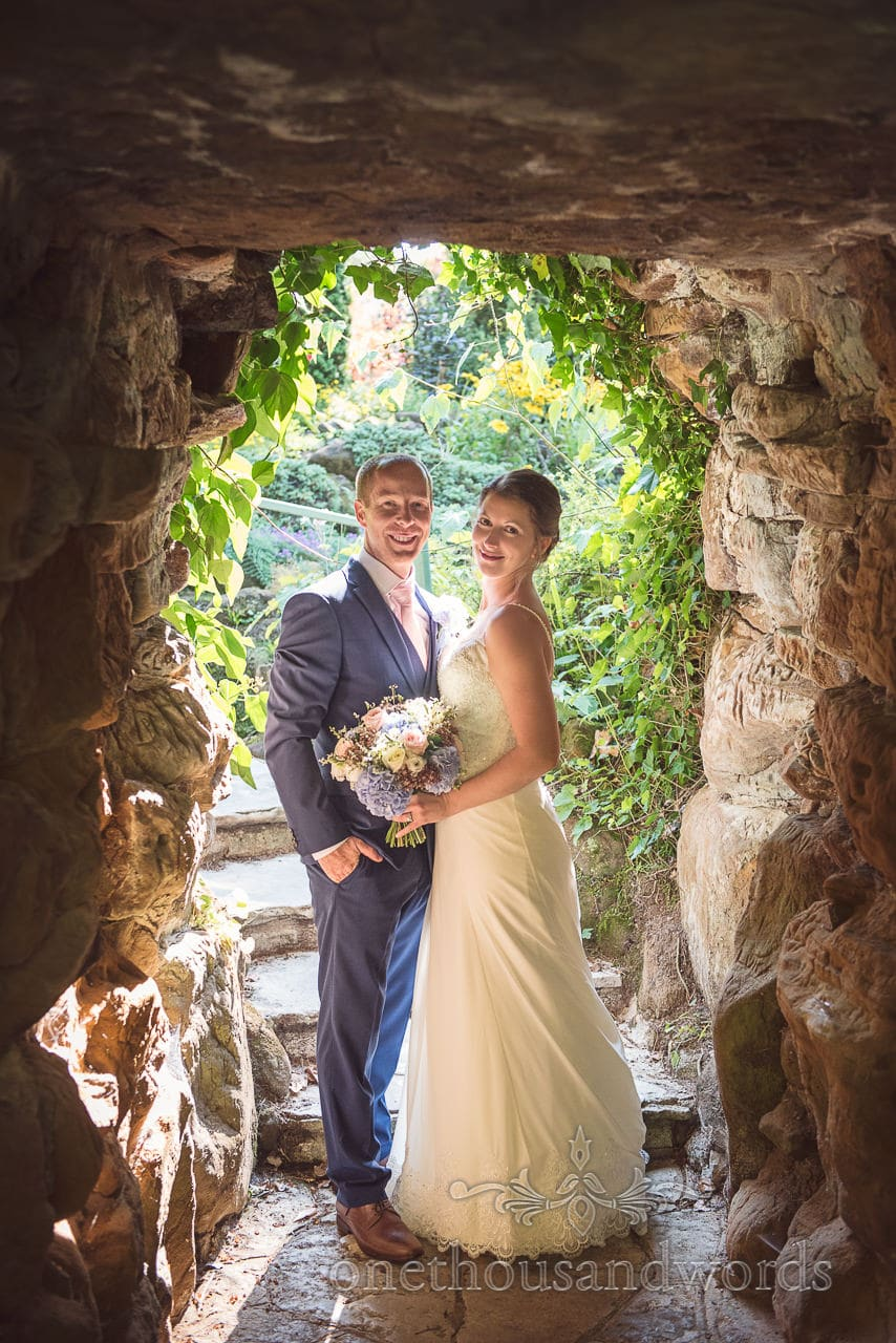 Smiling newlyweds in garden rock tunnel at the Italian Villa Wedding