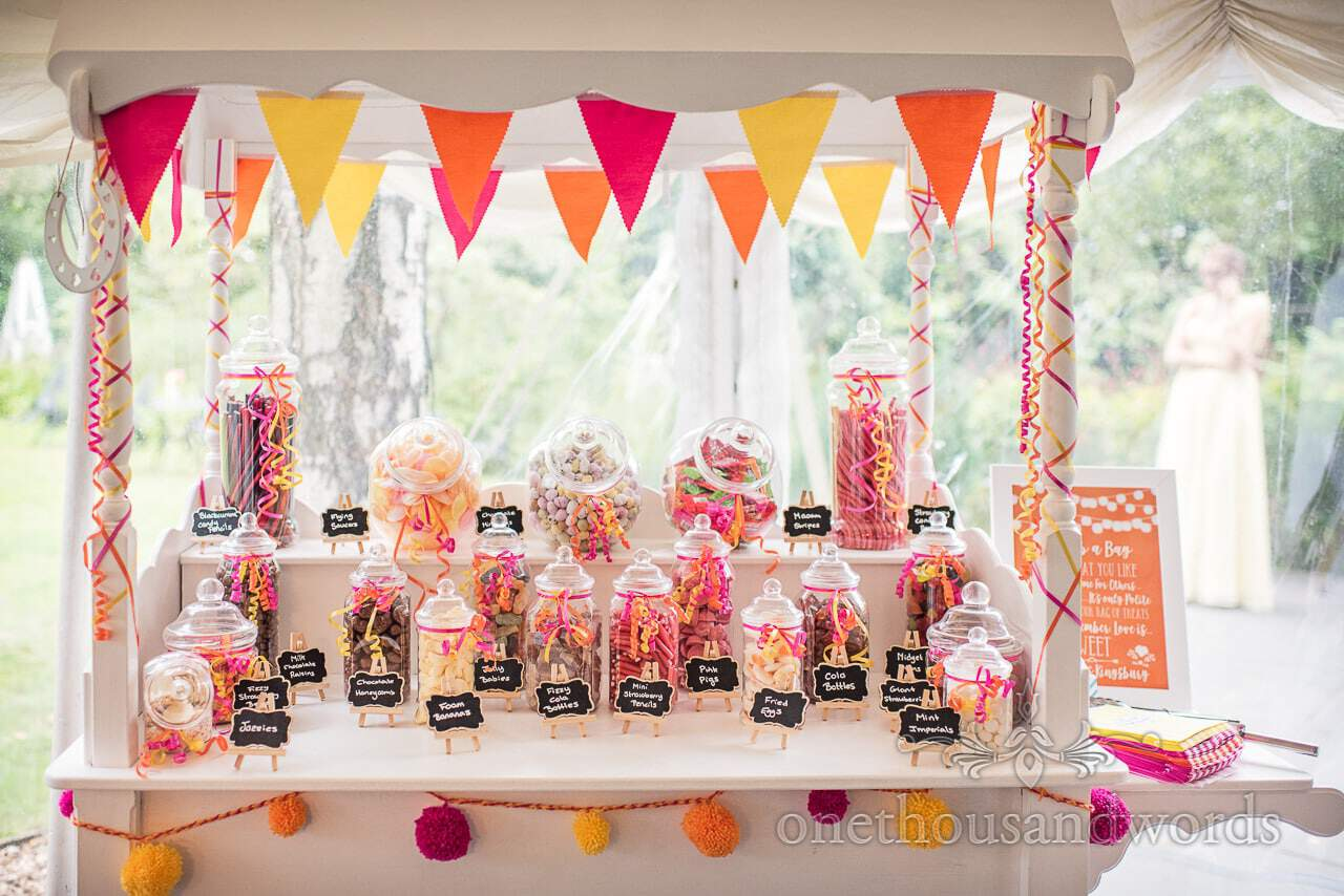 Stacked sweet cart with pink, yellow and orange bunting at The Old Vicarage Wedding