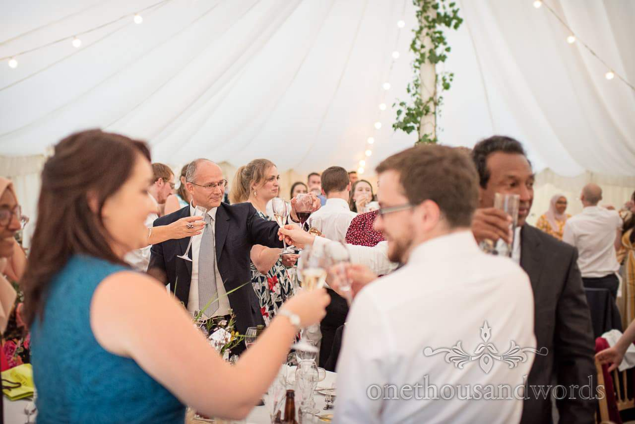 Standing guests raise a toast at marquee wedding reception