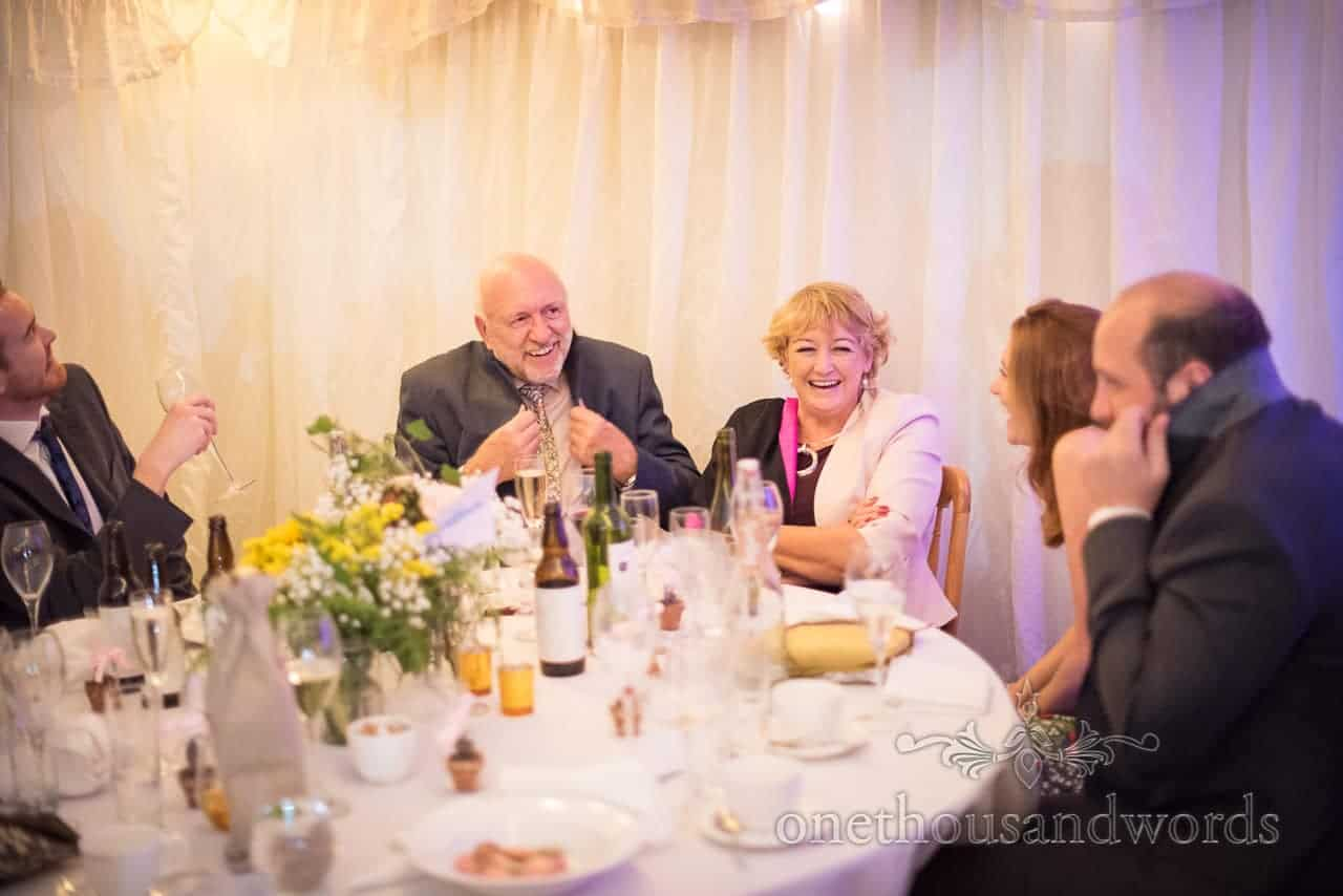 Table of guests share joke during evening wedding reception
