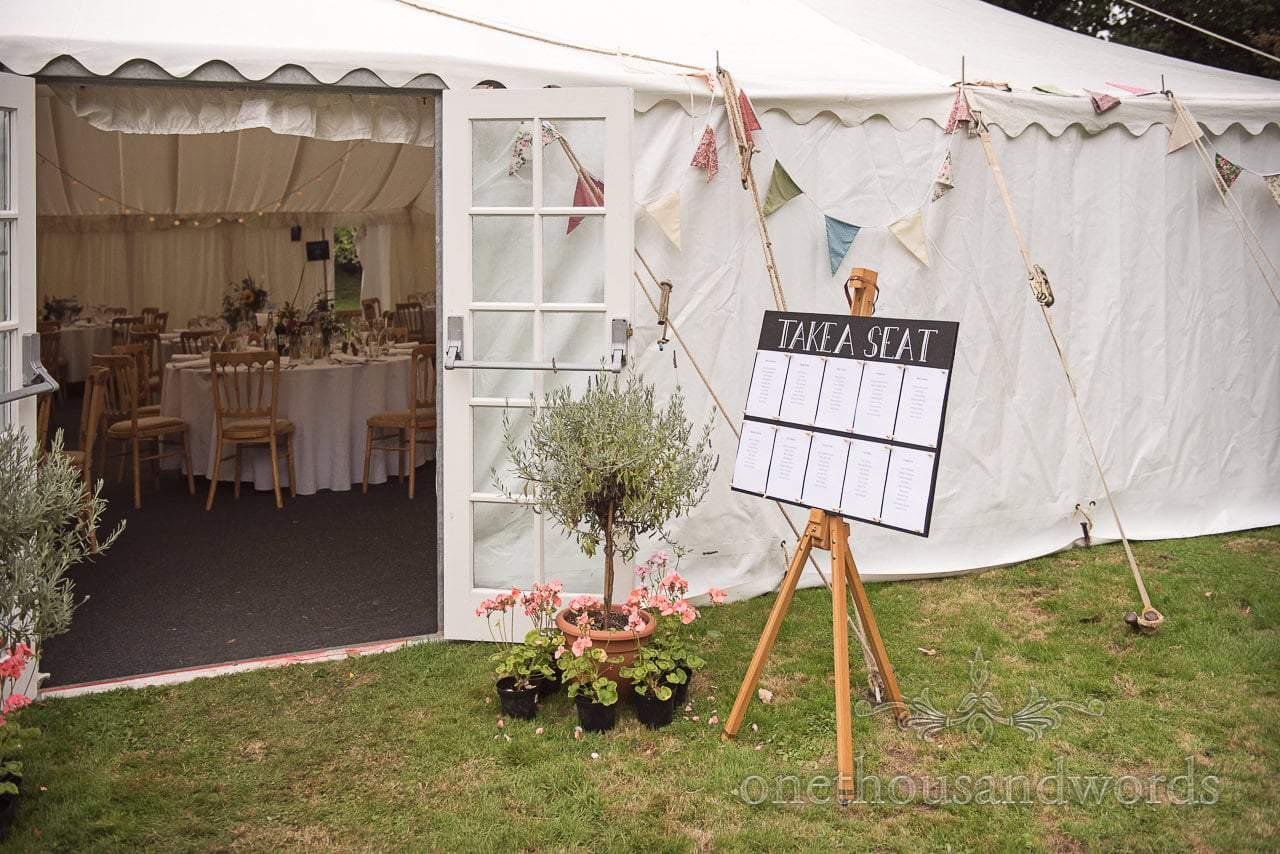 Table plan outside marquee at garden wedding reception