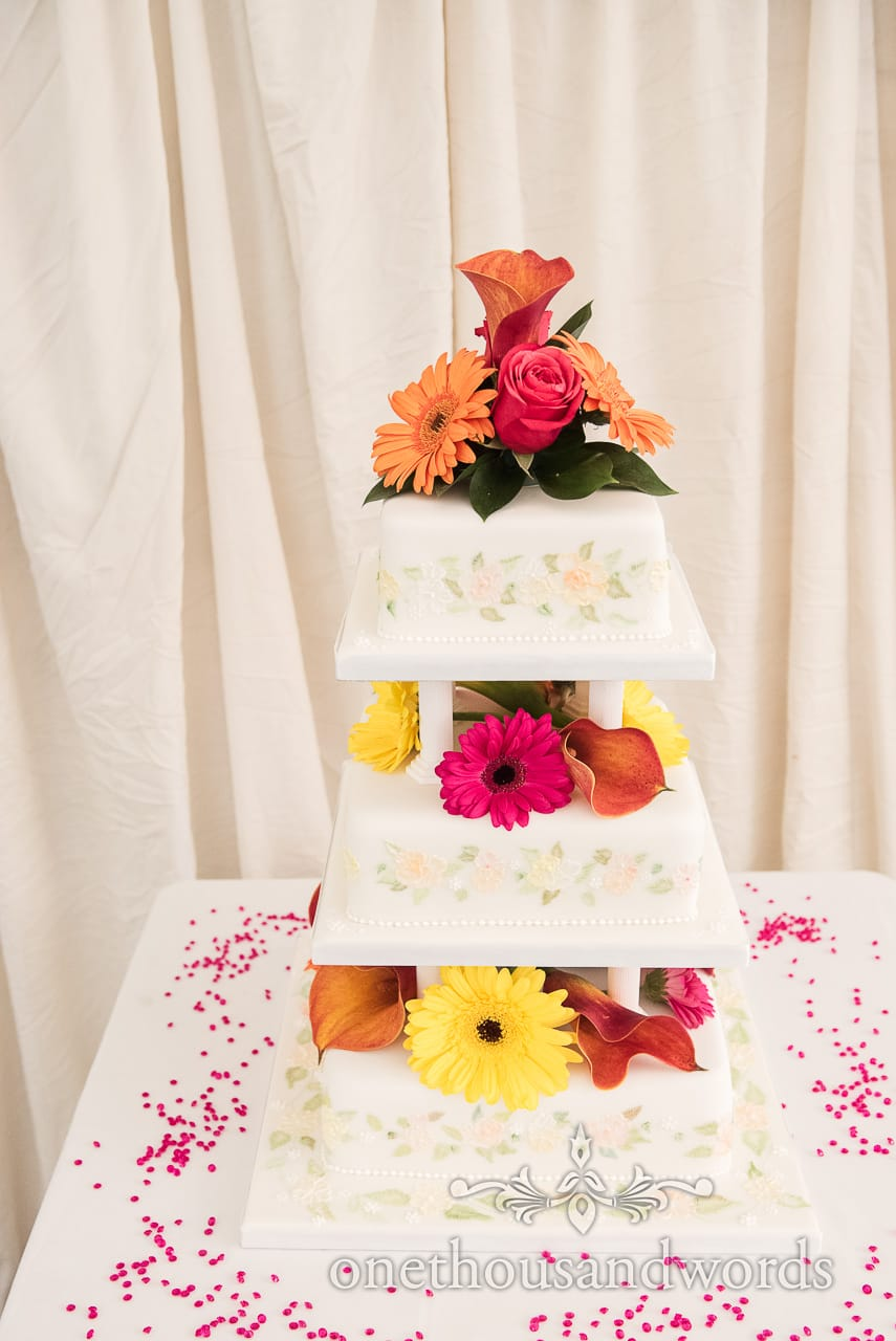 Three tiered wedding cake decorated with bright flowers at Old Vicarage Wedding