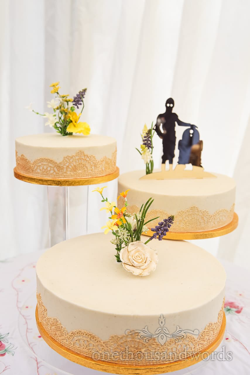 Three tiers of wedding cake with Star Wars cake topper at garden wedding