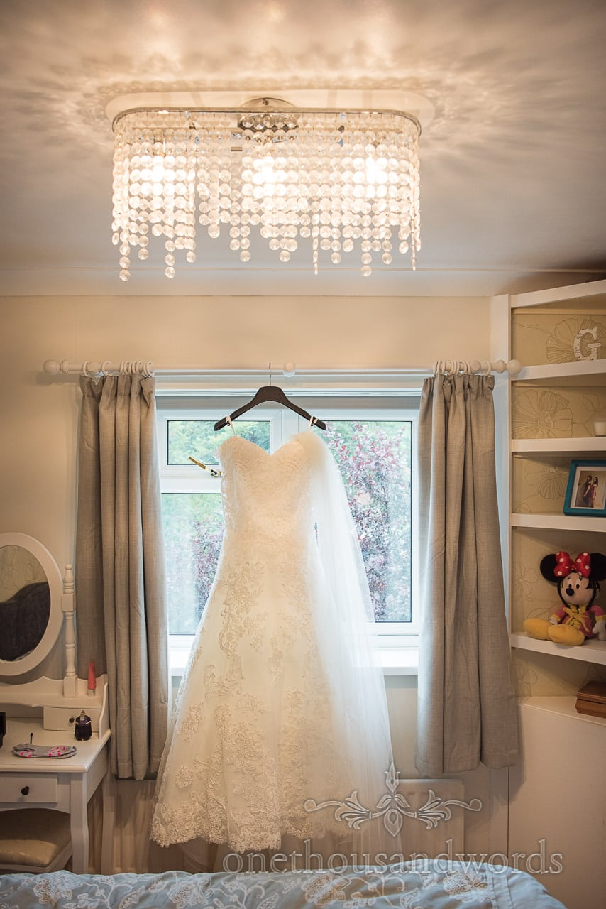 Wedding dress hangs in bedroom with amazing chandelier and childhood toys