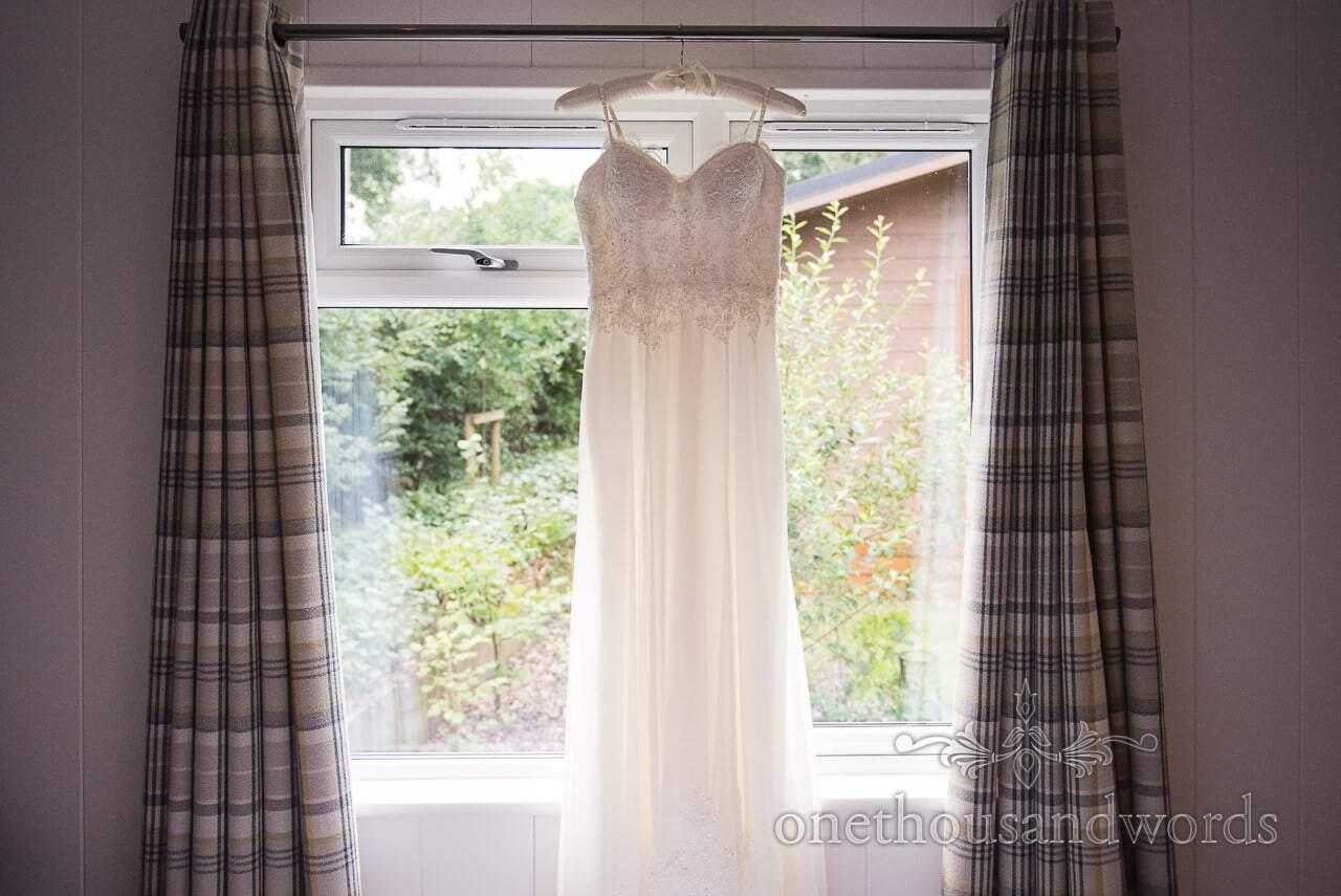 Wedding dress with lace detail hangs in lodge window before Italian Villa Wedding
