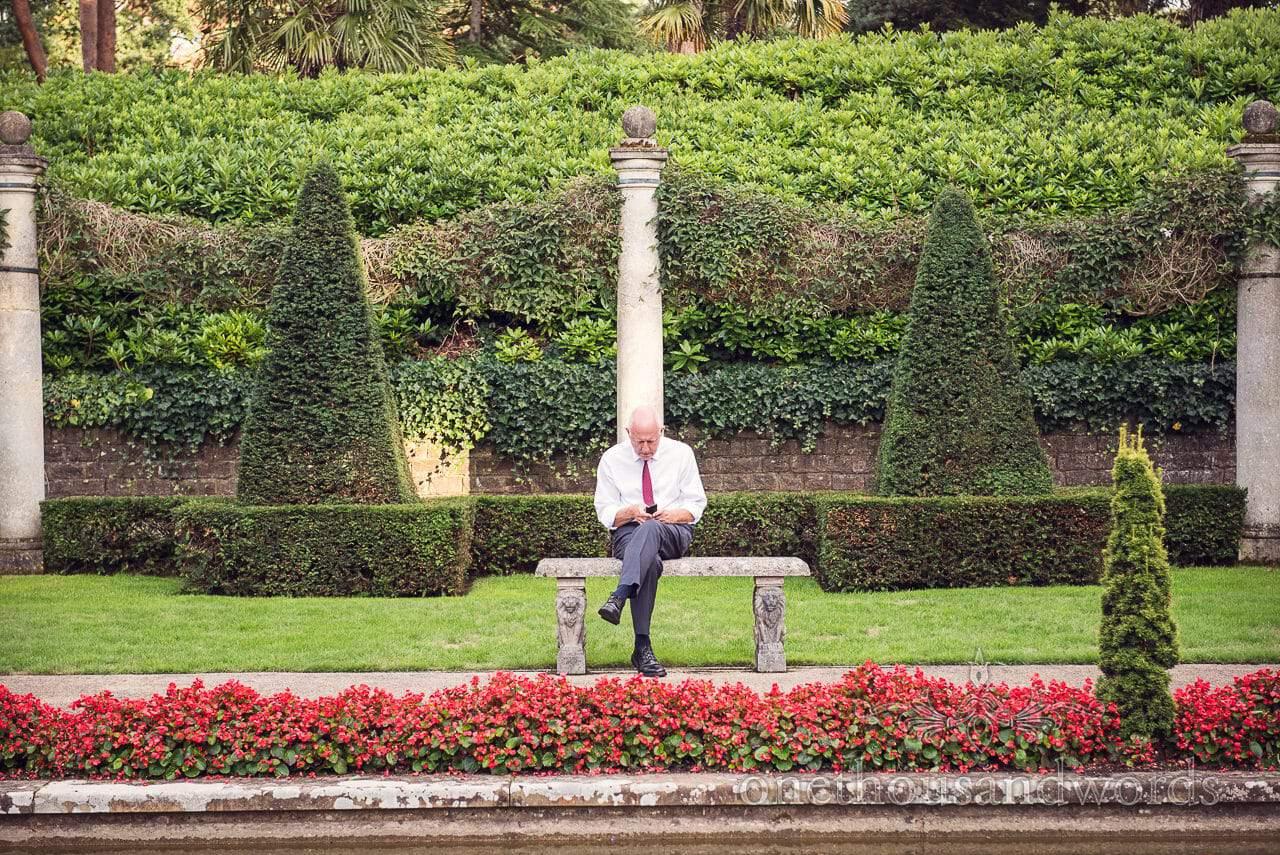 Wedding guest sits on stone bench in the Italian Villa Wedding venue gardens