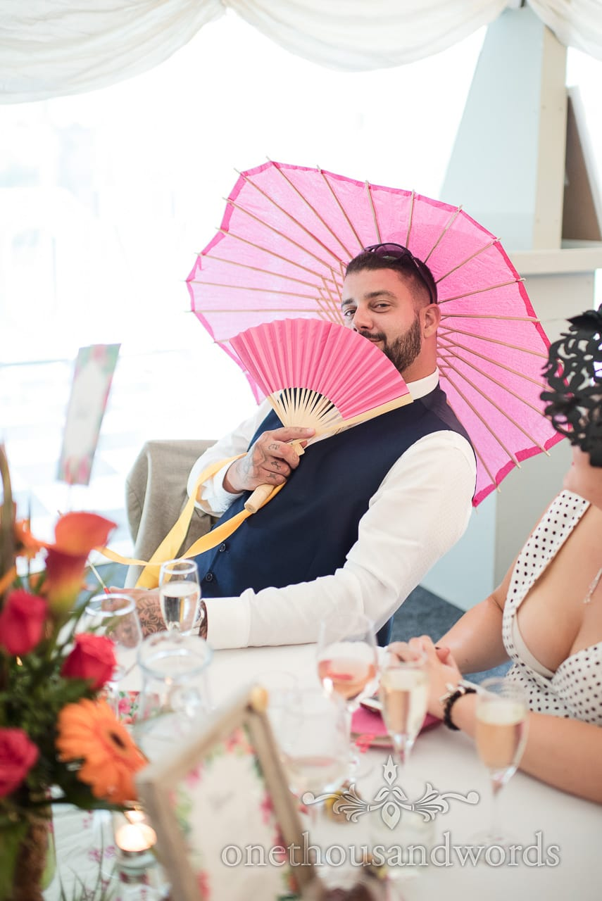 Wedding guest with pink fan and umbrella at The Old Vicarage Wedding