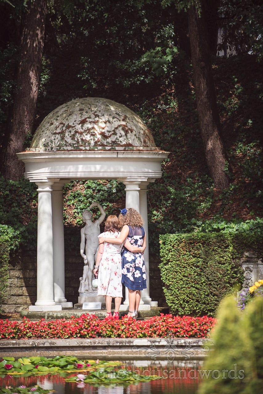 Wedding guests admire stone statue in Italian Gardens at The Italian Villa Wedding