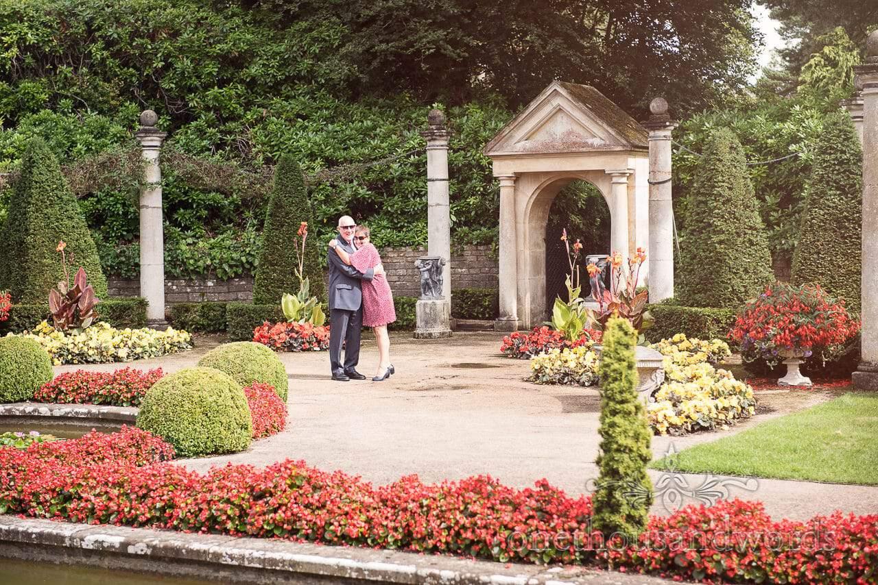 Wedding guests hugging in the Italian Gardens at the Italian Villa Wedding venue