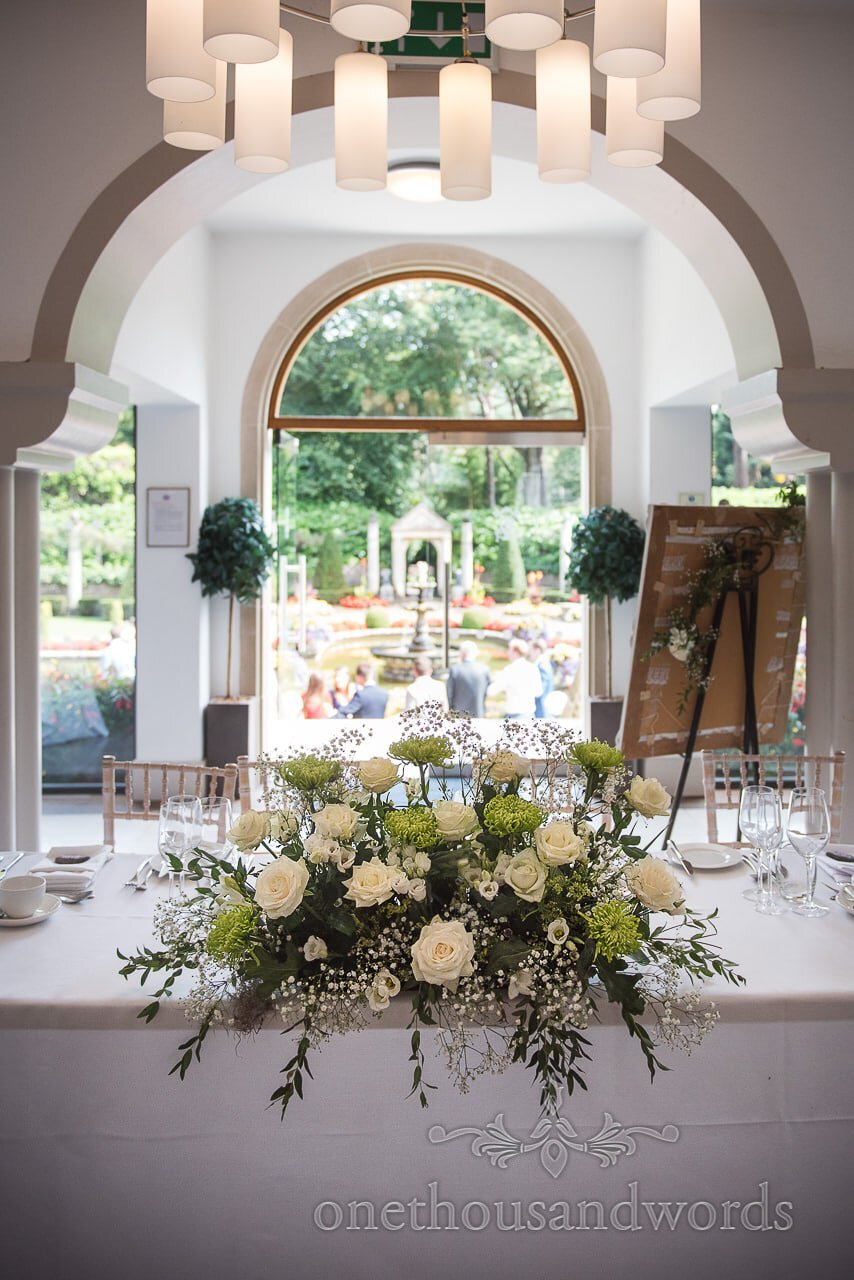 White and green floral wedding spray on top table at The Italian Villa wedding venue