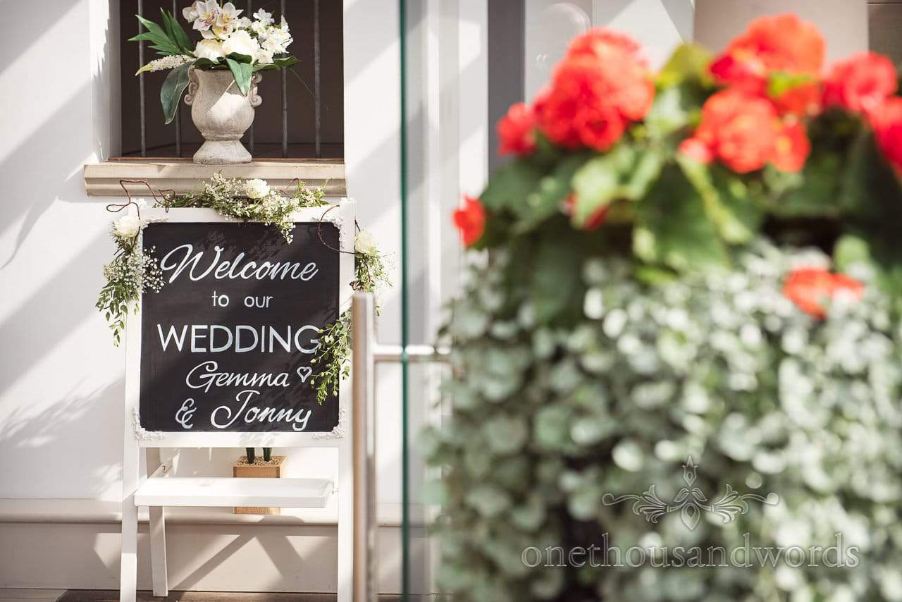 White framed welcome to wedding sign with green and white flowers