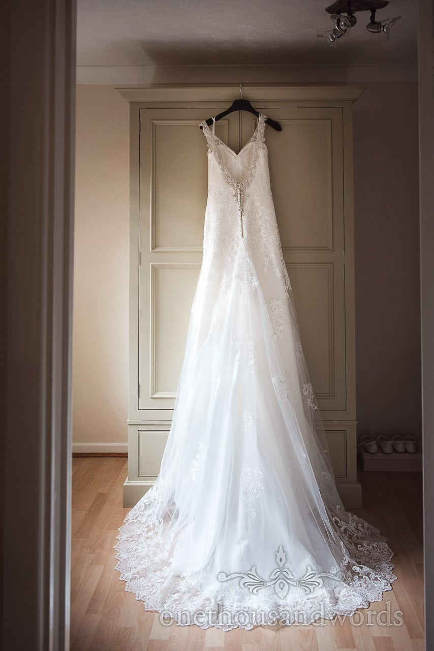 White lace detailed dress hangs on morning of Canford School Wedding Photographs
